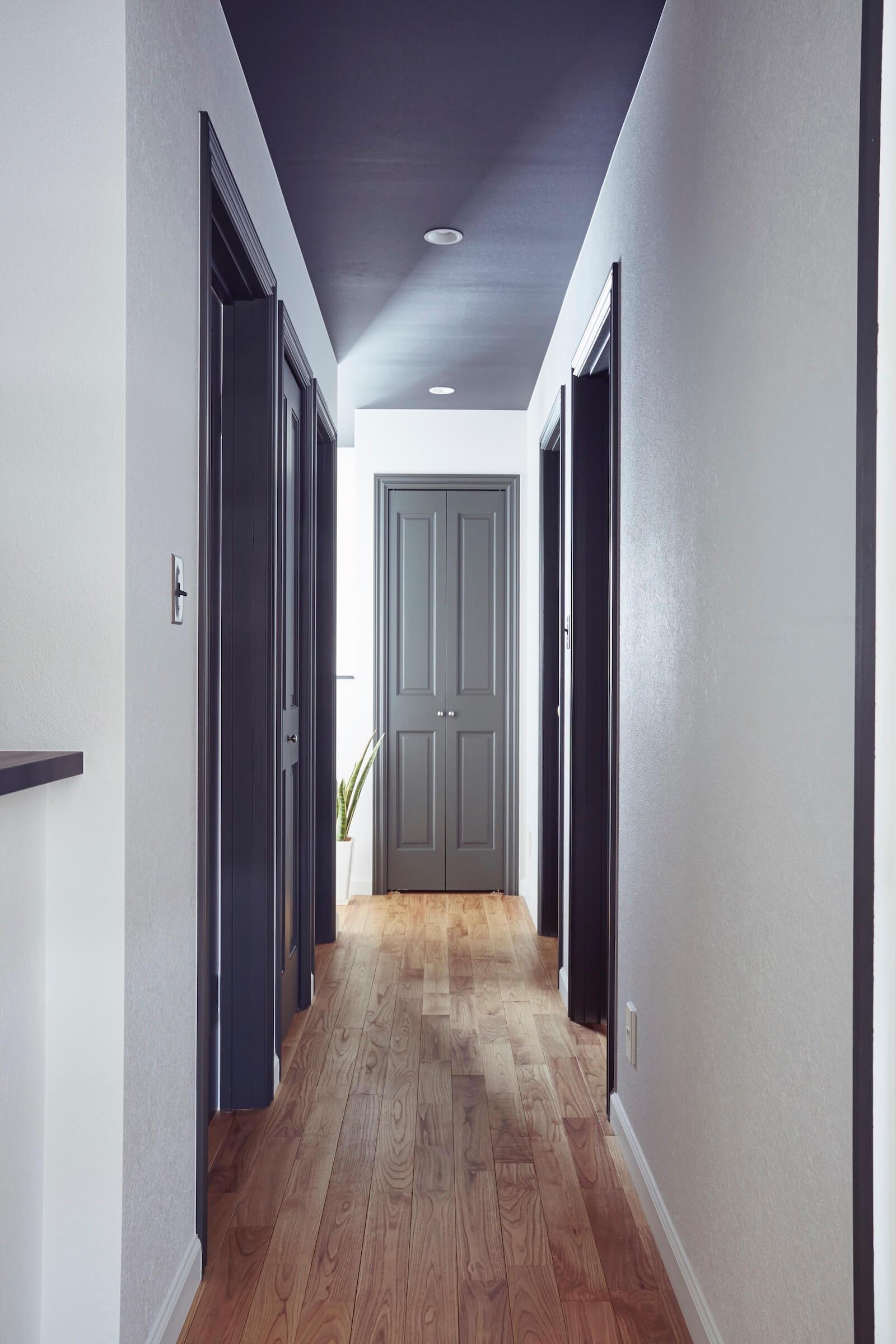 ラップサイディングのビルトインガレージの廊下と木製ドア
